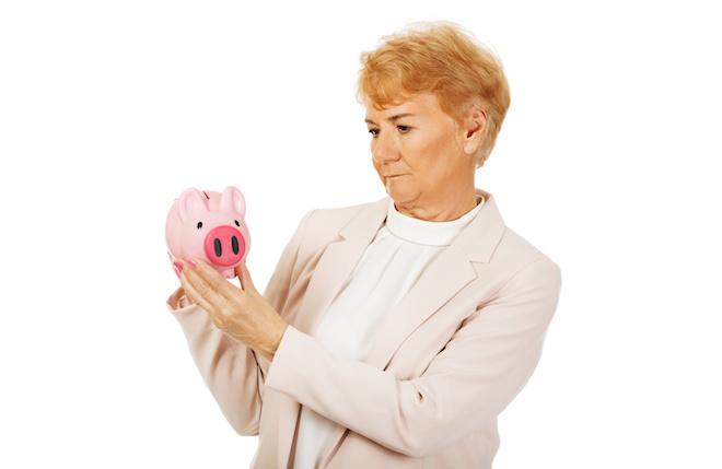 Pensive elderly woman holding piggy bank
